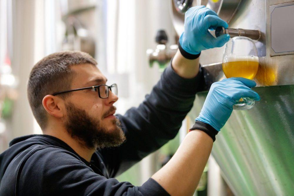Bryggmästare testar öl från en fermenteringstank